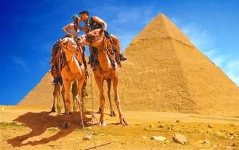A couple riding a camel in the Pyramids of Giza, Cairo, Egypt